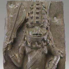 <p>African Galleries, Level 2</p> <p>The royal regalia of this Benin Chief, including a paddle-shaped sword, leopard-tooth necklace, and other rich apparel, communicate his power and status within Benin culture. What else about him tells us he is powerful?</p>