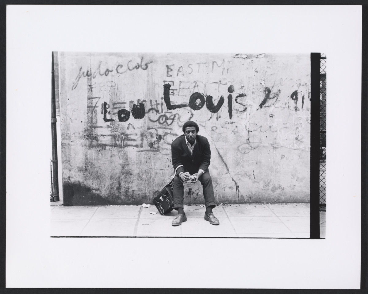 "Black and white photograph of Lou Draper leaning against a wall holding a camera. Graffiti above his head says ""Lou"" and ""Louis""."