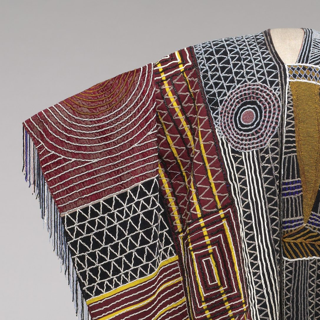 <p>In a nearby room in the African Art Gallery, look for the work of art that includes this detail. Who wore this colorful robe? Have you ever made a cape or robe using a piece of cloth? </p> <p>How do folds and darts change flat cloth into clothing that can be worn by a person? </p>
